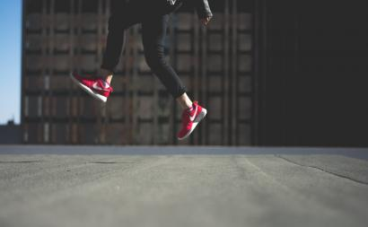 Woman wearings Nike shoes jumping in the air.