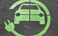 An electric car charging symbol on pavement.