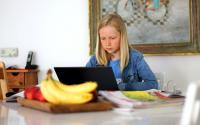 Blonde girl doing schoolwork at home. Photo via Pixabay.